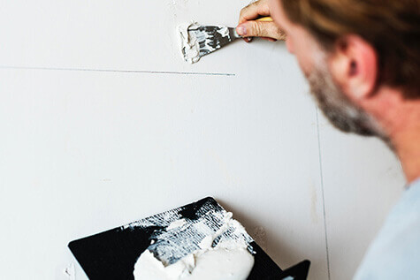 Middle aged man holding the brush, painting a wall white.